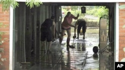 Local residents clear away the mud from their flooded home in Brisbane, Australia. Parts of Brisbane reopened as deadly floodwaters that had swamped entire neighborhoods recede, revealing streets and thousands of homes covered in a thick layer of putrid