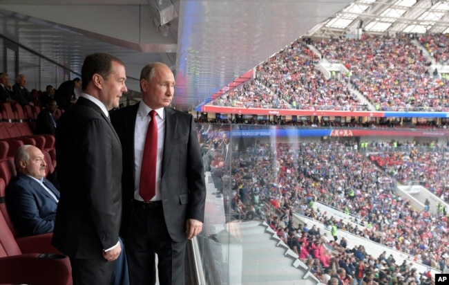 El presidente ruso, Vladimir Putin, (derecha) y el primer ministro ruso, Dmitry Medvedev, observan el partido entre Rusia y Arabia Saudita que dio inicio al Mundial Rusia 2018 en Moscú, el 14 de junio de 2018.