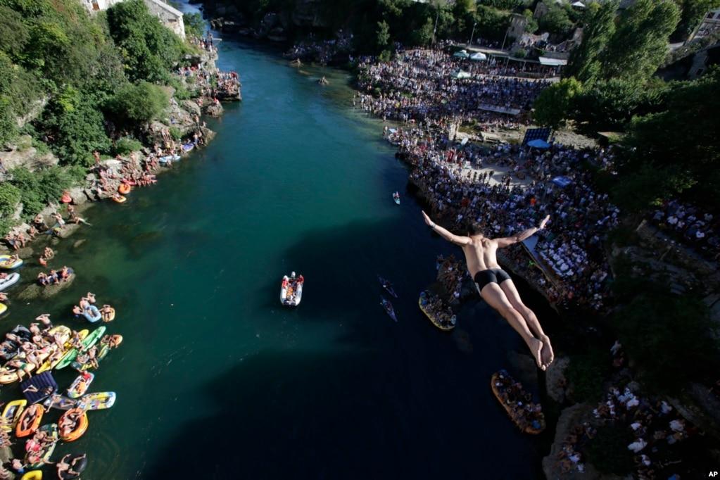 波斯尼亚首都萨拉热窝以南140公里处,2017年7月30日,在莫斯塔尔举行的第451届高台跳水比赛中,运动员从桥上跳水。