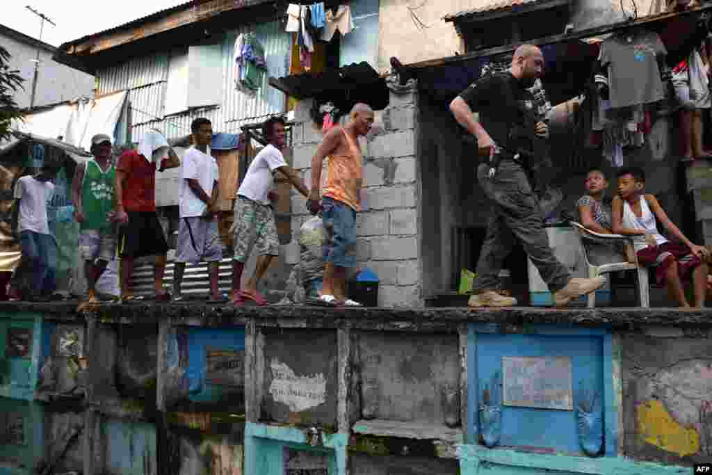 An agent (R) of Philippine Drug Enforcement Agency (PDEA) escorts suspects during a raid at an informal settlers' area inside a public cemetery in Manila. President Rodrigo Duterte handed the drug war campaign over to the much smaller Drug Enforcement Agency, with support from the military, in late January.