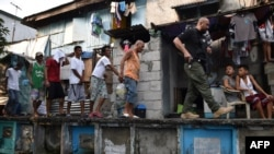 FILE An agent (R) of Philippine Drug Enforcement Agency (PDEA) escorts suspects during a raid at an informal settlers' area inside a public cemetery in Manila on March 16, 2017.