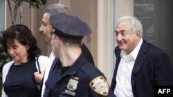 Ông Dominique Strauss-Kahn (sau) rời khỏi nhà, cùng với vợ, lần đầu tiên sau lệnh quản chế ông được rút lại