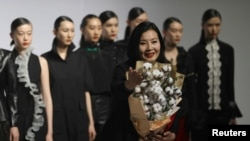 时装设计师周丽在北京举行的中国国际时装周上怀抱一把棉花做出的花束表达对新疆棉的支持。(2021年3月30日)