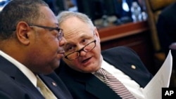 """Mississippi state Sen. Eugene """"Buck"""" Clarke, right, confers with Sen. Robert Jackson, Feb. 5, 2019, in Jackson, Miss. Clarke's district is to be redrawn by order of a federal appeals court. Clarke is not seeking re-election."""