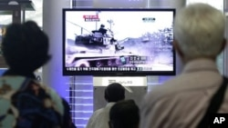 People watch a TV news program showing video footage of a South Korean army tank during a past exercise at Seoul Railway Station in Seoul, South Korea, Wednesday, Aug. 10, 2011. South Korean marines returned fire Wednesday after North Korea launched artil