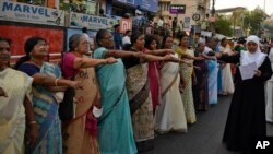 "Women raise their hands to take a pledge to fight gender discrimination as they form part of a hundreds kilometer long ""women's wall"" in Thiruvananthapuram, in the southern Indian state of Kerala, Tuesday, Jan. 1, 2019. (AP Photo/R.S. Iyer)"