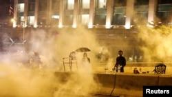 反政府抗議者11月18日在香港理工大學外身處警方催淚彈的濃霧中。