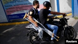 People ride on a motorcycle as they leave after rehabilitation therapy in a public hospital in Caracas, Oct. 28, 2013.