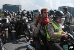 FILE - In this April 24, 2017, photo, Bolivarian National Police officers ride away on a motorcycle with a detained anti-government protester, in Caracas, Venezuela.