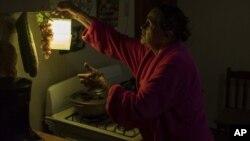 En esta imagen, tomada el 12 de julio de 2018, Marta Bermúdez Robles, de 66 años, cuelga una lámpara en su cocina, en Adjuntas, Puerto Rico, ante la falta de electricidad desde el paso de los huracanes Irma y María.