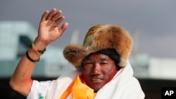 FILE - In this May 20, 2018, file photo, Nepalese veteran Sherpa guide, Kami Rita, 48, waves as he arrives in Kathmandu, Nepal. Rita has scaled Mount Everest for a 23rd time, breaking his own record for the most successful ascents. (AP Photo/Niranjan Shrestha, File)