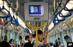 A TV screen shows the news of Edward Snowden, a former CIA employee who leaked top-secret documents about sweeping U.S. surveillance programs, in the underground train in Hong Kong Sunday, June 16, 2013.