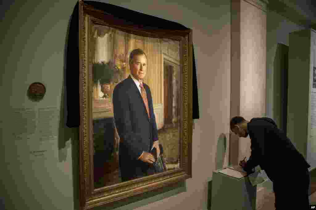 Ameer Hassan of New York stops to sign the condolence book as the official portrait of former President George H.W. Bush is draped in black cloth at the National Portrait Gallery in Washington, Dec. 3, 2018, to mark his passing.