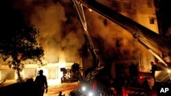 Спасатели работают на месте крупного пожара на швейной фабрике в Дакке, Бангладеш. 24 ноября 2012 года