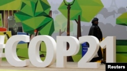 FILE - A woman walks past the COP21 logo in the Climate Generations area during the World Climate Change Conference 2015 (COP21) at Le Bourget, near Paris, France, Dec. 1, 2015.