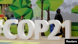 A woman walks past the COP21 logo in the Climate Generations area during the World Climate Change Conference 2015 (COP21) at Le Bourget, near Paris, France, Dec. 1, 2015.