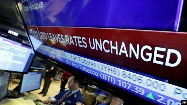 A television screen on the floor of the New York Stock Exchange shows the rate decision by the Federal Reserve, Jan. 27, 2016.
