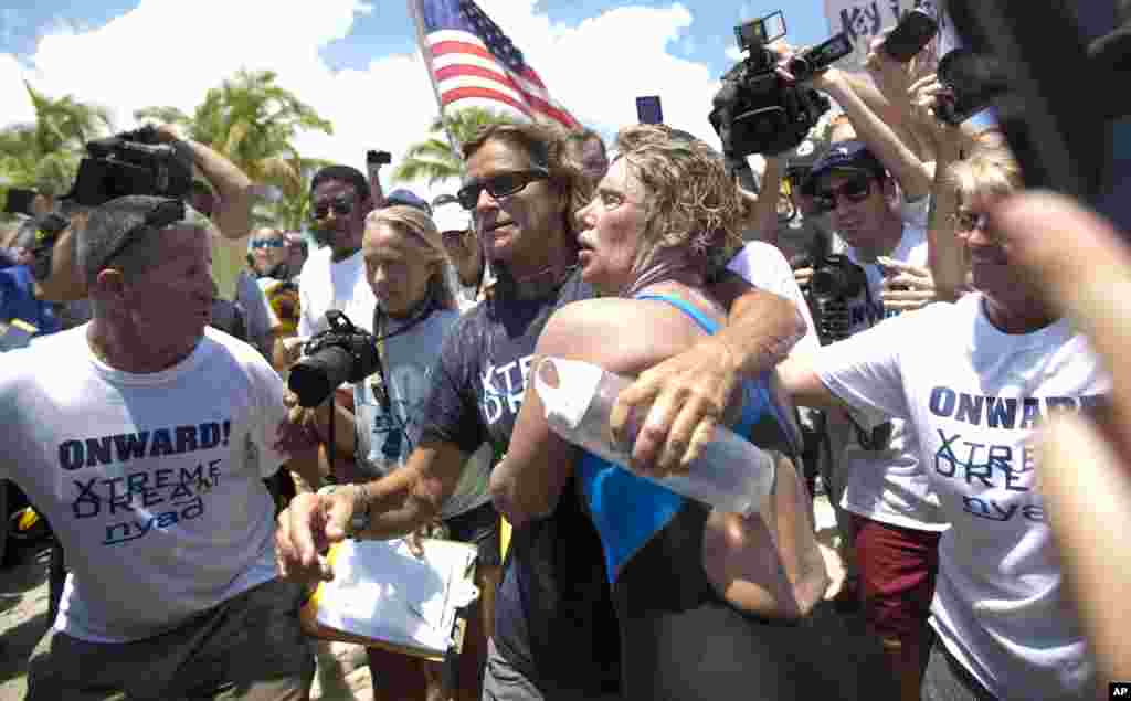 Endurance swimmer Diana Nyad, right, and her trainer, Bonnie Stoll hug after Nyad walks ashore in Key West, Florida, Sept. 2, 2013.