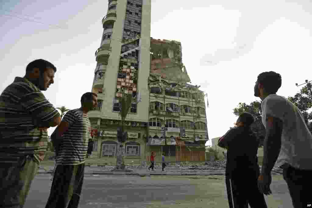 Palestinians inspect the damage of the Al-Shalam (Peace) tower, destroyed by an overnight Israeli strike, in Gaza City, July 22, 2014.