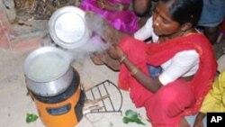 Một phụ nữ Ấn Độ dùng một bếp lò đốt bằng củi nhưng ít khói