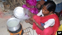 FILE - A woman in India is uses a cookstove that produces less smoke for burning wood or any other fuel.