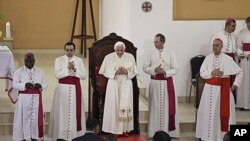 Pope Benedict XVI, center, takes his place as he arrives at the basilica in Ouidah, Benin, November 19, 2011.
