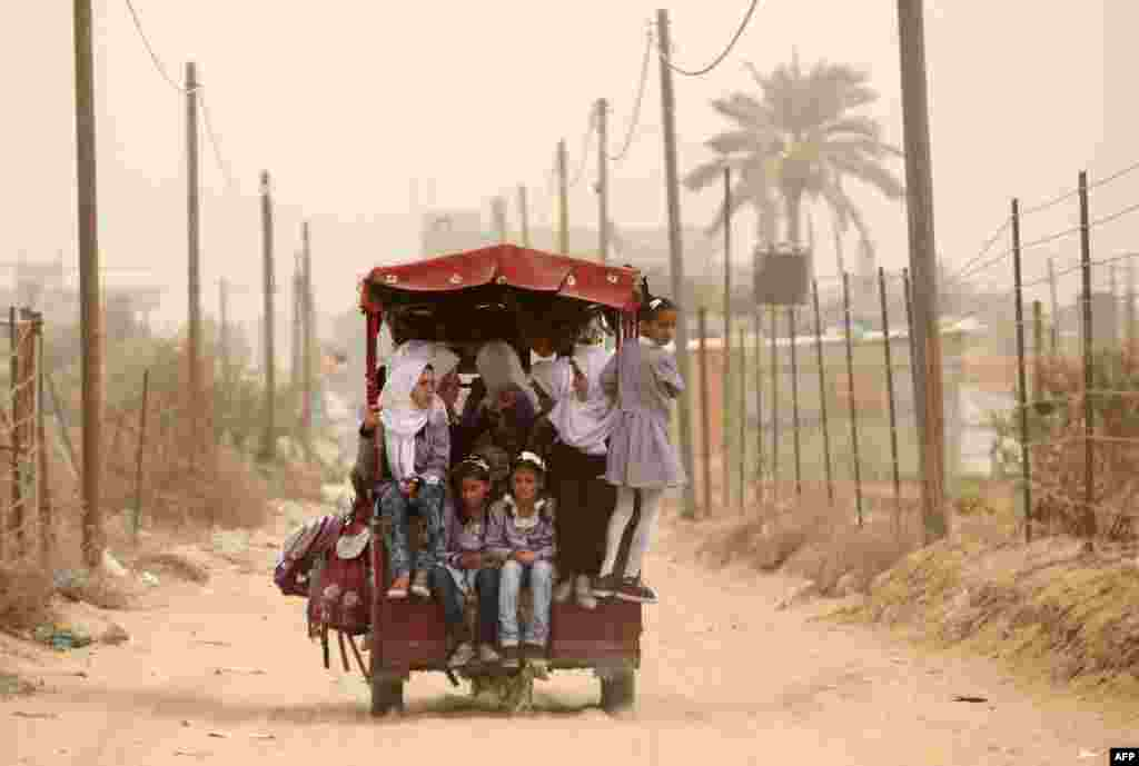 Palestinian school children ride a rickshaw during a sandstorm in Khan Yunis in the southern Gaza Strip. A dense sandstorm engulfing parts of the Middle East left at least eight people dead and hundreds suffering from respiratory problems, as officials warned residents to stay indoors.