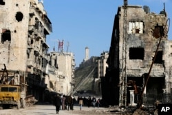 Residents walk through damaged buildings near to the ancient Aleppo Citadel, background, that government troops used as a military base in the old city of Aleppo, Syria, Jan. 21, 2017.