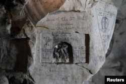 Inscriptions by WWI Private David McAlpine, 2nd Highland Light Infantry, are seen on the rock wall in underground caves accessible by small spiral stairs in the village's church at Bouzincourt, northern France, July 13, 2015.