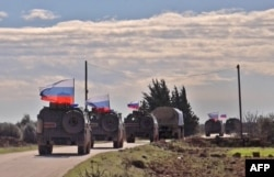 FILE - An image grab taken from AFP-TV shows Russian army vehicles on patrol in the area of Arimah, just west of Manbij, Syria, Jan. 17, 2019.