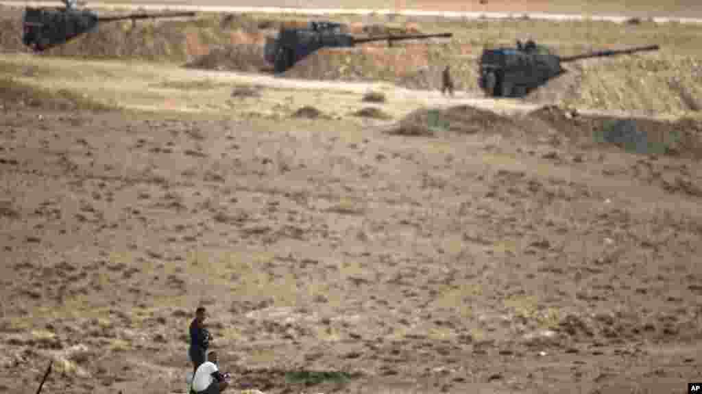 Người Kurd phía bên kia biên giới theo dõi cuộc chiến ở thị trấn Kobani từ một đỉnh đồi ở ngoại ô Suruc, Thổ Nhĩ Kỳ.
