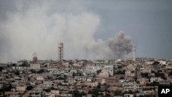 FILE - Smoke rises after a TNT bomb was thrown from a helicopter, hitting a rebel position during heavy fighting between troops loyal to Syrian President Bashar al-Assad and opposition fighters, near Kafr Nabuda, Idlib province, Syria, Sept. 19, 2013.