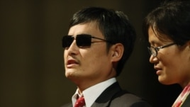 FILE - Blind Chinese activist Chen Guangcheng (l), accompanied by his wife Yuan Weijing.