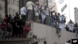 مصر میں مظاہرین امریکی سفارت خانے کی دیوار پر چڑھے ہوئے ہیں