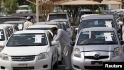 FILE - People check used cars displayed for auction at Al Aweer Market in Dubai, UAE, April 8, 2018.