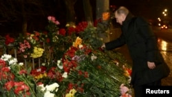 Russia's President Vladimir Putin lays flowers at the site of an explosion on a trolley bus in Volgograd January 1, 2014.