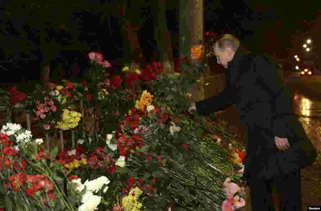 Russian President Vladimir Putin lays flowers at the site of a trolley bus explosion, Volgograd, Russia, Jan. 1, 2014.