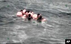 Anggota awak kapal nelayan China yang terbalik di Pulau Ishigaki, prefektur Okinawa, Jepang selatan pada hari Selasa, 2 Maret 2021, tertangkap oleh kamera yang dipasang pada pesawat dan dirilis oleh Markas Penjaga Pantai Regional Jepang ke-11. (Foto: Penjaga Pantai Regional Jepang ke-11 via AP).
