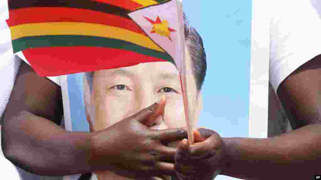 A woman holds a portrait of Chinese President Xi Jinping while welcoming him in Harare, Zimbabwe, Tuesday, Dec. 1, 2015. Jinping is in Zimbabwe for a two day State visit during which he is set to sign some bilateral agreements aimed at strengthening relationships between the two countries.