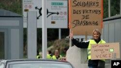 """Un manifestante sostiene una pancarta que dice """"Todos juntos, pónganse sus chalecos amarillos y vengan"""", en Biarritz, suroeste de Francia."""