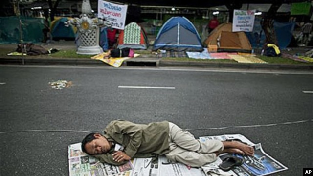 A supporter of the People's Alliance for Democracy, also known as the Yellow Shirts, sleeps on the street near Government House in Bangkok, Thailand, January 27, 2011