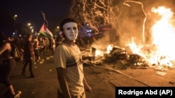 A masked anti-government protester stands by a burning barricade in Santiago, Chile, Monday, Oct. 28, 2019.