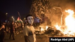 A masked protester stands by a burning barricade in Santiago, Chile, Monday, Oct. 28, 2019. (AP Photo/Rodrigo Abd)