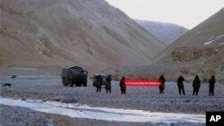 """Tentara China merentangkan spanduk bertuliskan """"Anda telah melewati garis perbatasan. Silakan mundur"""" di Ladakh, India (5/5). India dan China telah sepakat mengakhiri ketegangan yang telah berlangsung selama tiga minggu terkait sengketa wilayah perbatasan di Himalaya ini."""