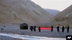 """Quân đội Trung Quốc cầm biểu ngữ với hàng chữ: """"Bạn đã vượt qua biên giới, xin vui lòng quay trở lại"""" tại Ladakh, Ấn Độ, ngày 5/5/2013."""