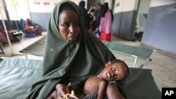 A woman holds her malnourished child on arrival at Banadir hospital in Mogadishu, Somalia, July 7, 2011