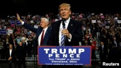 Republican U.S. presidential nominee Donald Trump (R) and vice presidential candidate Mike Pence (L) hold a campaign rally in Cleveland, Oct. 22, 2016.