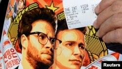 """ນາຍ Dennis Lavalle ຖືປີ້ ແລະປ້າຍຄຳຂວັນ ຮູບເງົາ """"The Interview"""" ທີ່ສະແດງໂດຍ Seth Rogen ແລະ James Franco."""