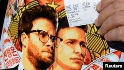 Một khán giả cầm chiếc vé và tấm quảng cáo phim The Interview, Los Angeles, California, 25/12/14