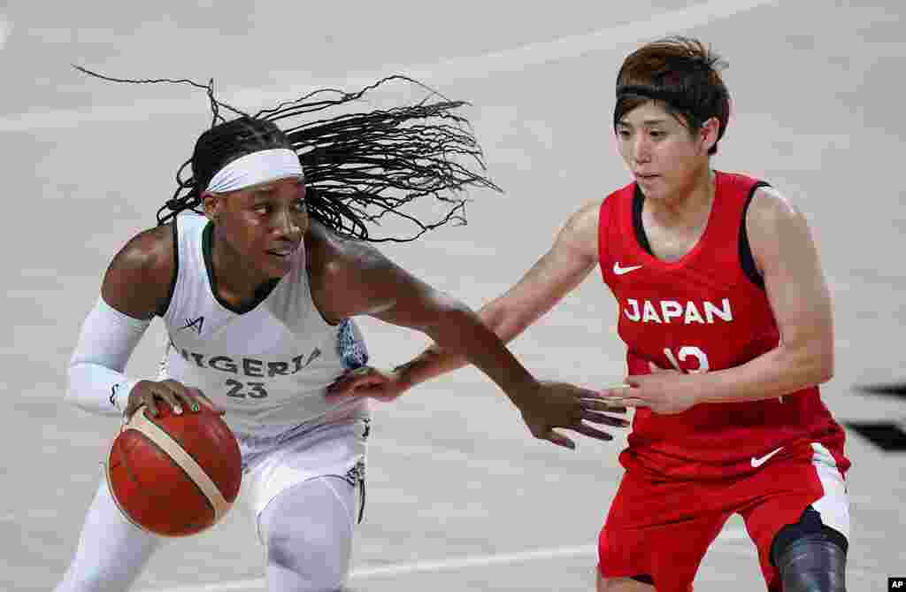 Nigeria's Ezinne Kalu (23) drives past Japan's Rui Machida (13), right, during women's basketball preliminary round game at the 2020 Summer Olympics, Monday, Aug. 2, 2021, in Saitama, Japan. (AP Photo/Charlie Neibergall)